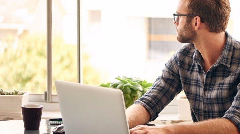 homem em frente a um computador estudando em casa